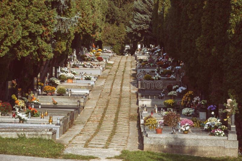 坟墓、墓碑和耶稣受难象在传统斯洛伐克公墓 奉献的蜡烛灯笼和花在坟茔石头在坟园 免版税库存照片