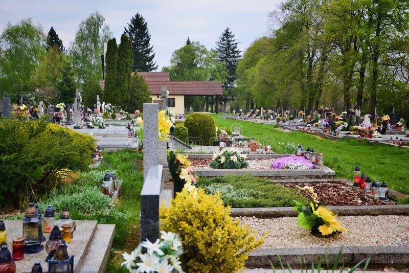 坟墓/墓碑在公墓/坟园 诸圣日天/所有尊敬/11月1日 花和蜡烛在坟茔石头 免版税库存图片