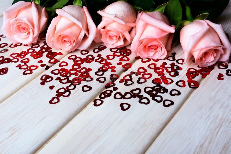 坠入爱河与淡粉红的玫瑰和小红色心脏的概念 免版税库存照片