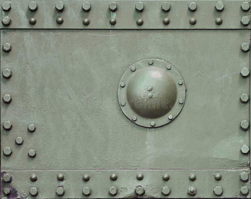 坦克的墙壁的纹理,由金属制成和加强与一许多螺栓和铆钉 覆盖物的图象  免版税库存照片