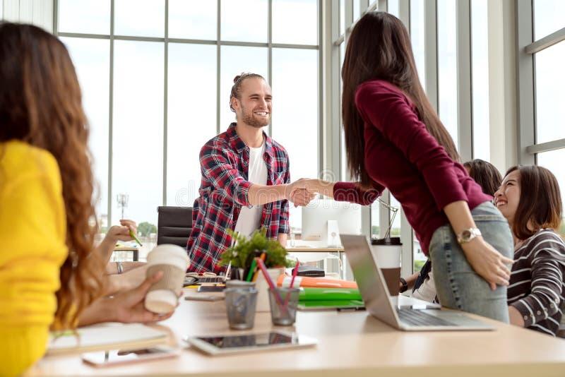 坦率年轻确信的白种人创造性的设计人微笑和与亚裔工友妇女或同事握手在办公室 免版税库存图片