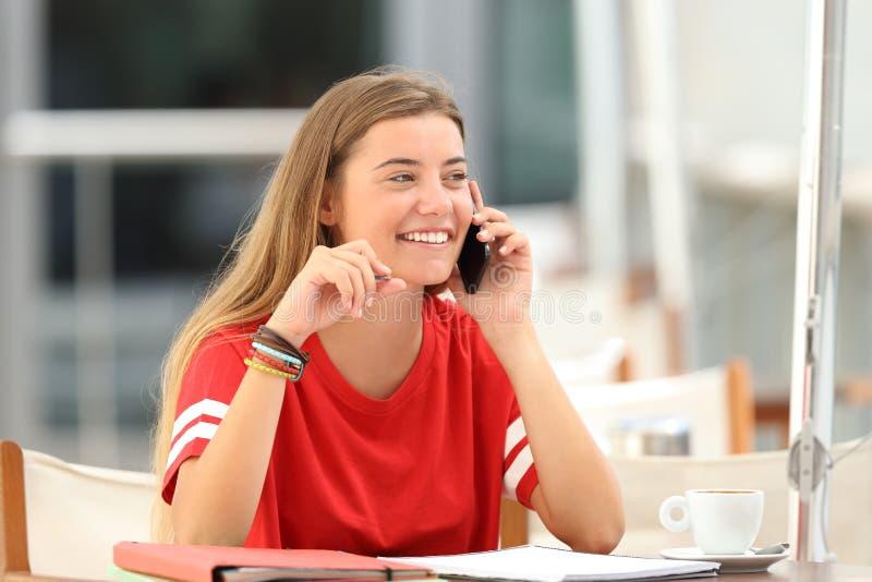 坦率的学生女孩谈话在酒吧的电话 免版税库存照片