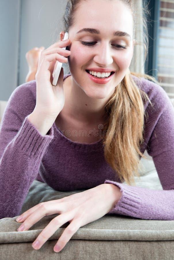 坦率的愉快的华美的十几岁的女孩画象谈话在电话 免版税库存照片