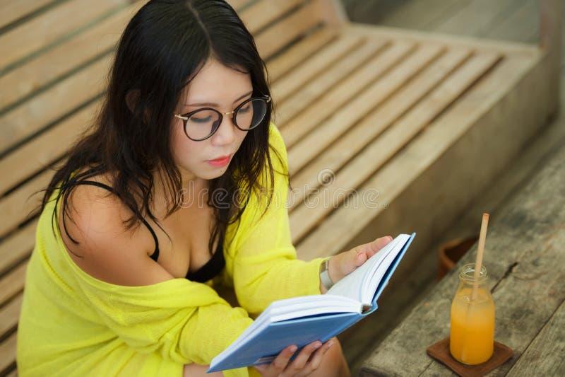 坦率的生活方式画象看书的年轻美丽和轻松的亚裔韩国学生女孩或学习户外在咖啡 免版税库存照片