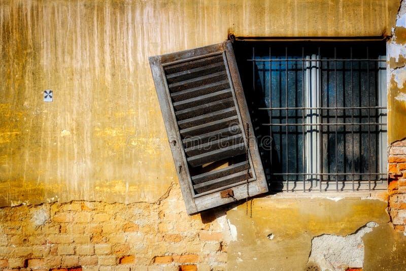 垂悬一个遗弃大厦的木快门 库存照片