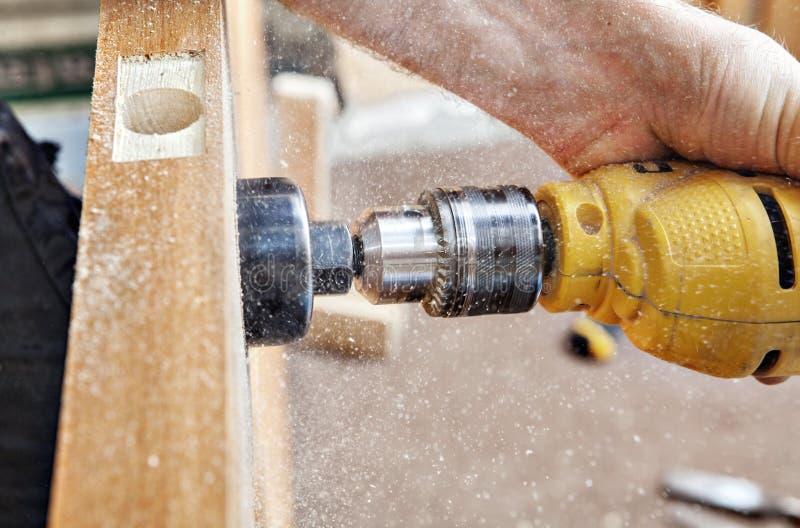 垂悬一个门,木匠钻锁门闩孔,特写镜头 图库摄影
