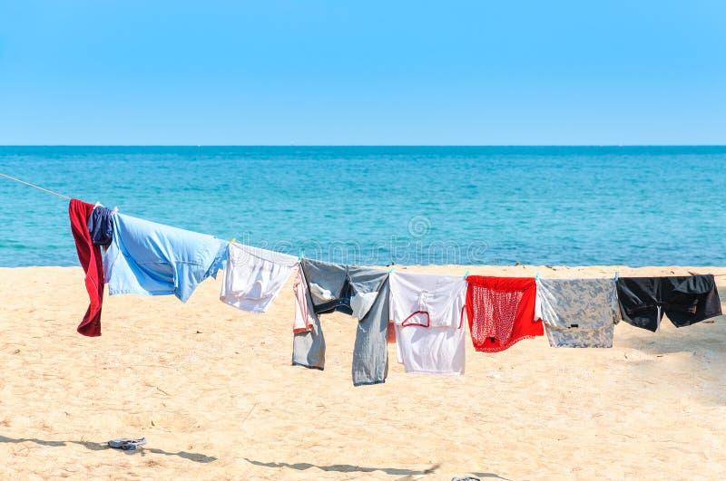垂悬五颜六色的衣裳烘干在洗衣店线和太阳shinin 免版税库存照片