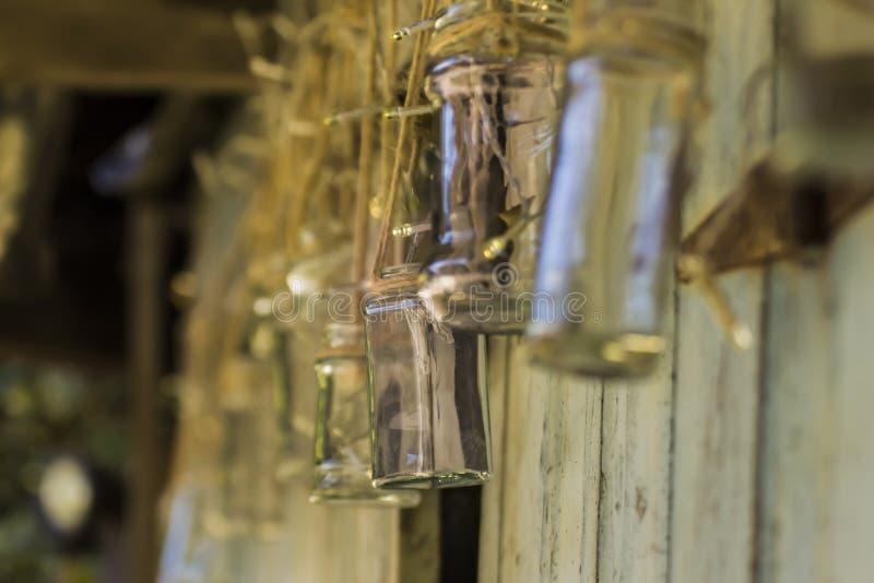 垂悬从串的玻璃瓶子一个失败的棚子外 免版税库存照片