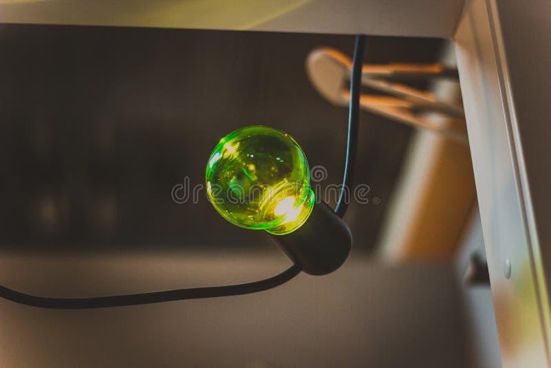 垂悬从天花板特写镜头的一个老绿灯电灯泡 库存照片