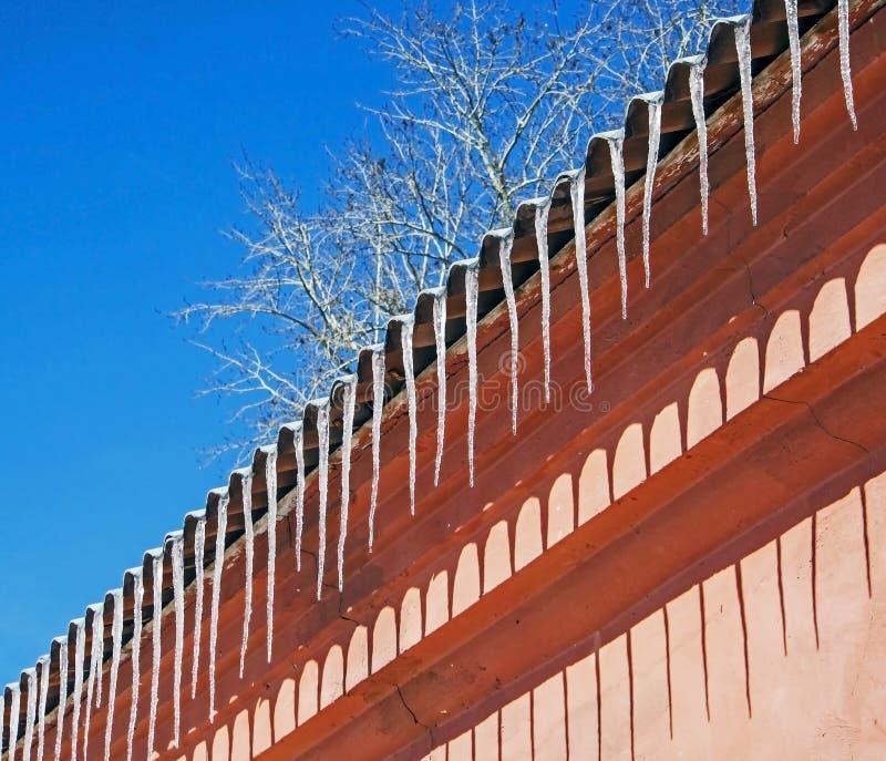 垂悬从屋顶的冰柱行点燃由太阳 库存图片
