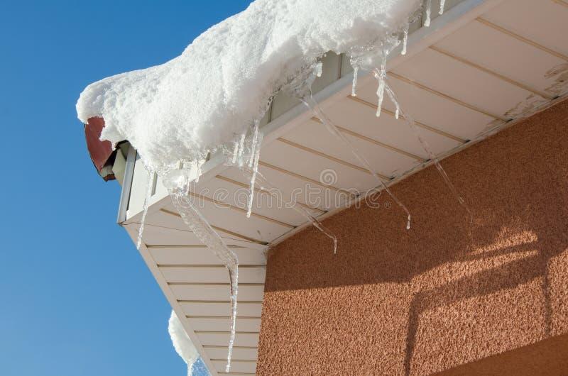 垂悬从屋顶的外缘的冰柱 熔化的冰和雪春天背景在好日子 免版税库存图片