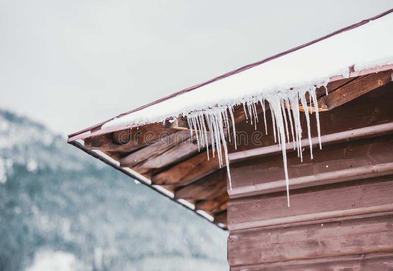 垂悬从山小屋屋顶的冰柱反对冬天多雪的风景 免版税图库摄影
