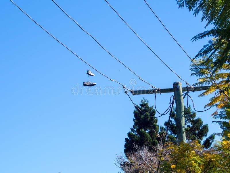 垂悬从电导线的鞋反对蓝天 库存照片