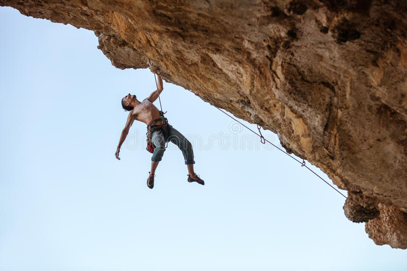 垂悬单手的男性攀岩运动员 免版税库存照片