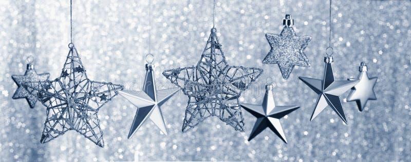 垂悬反对闪烁背景的银色星 免版税图库摄影