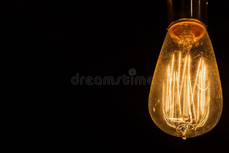 垂悬反对黑背景的葡萄酒爱迪生电灯泡 图库摄影