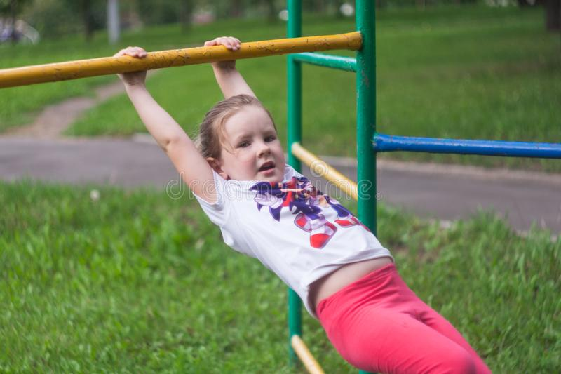 垂悬和摇摆在手上的女孩 免版税库存照片