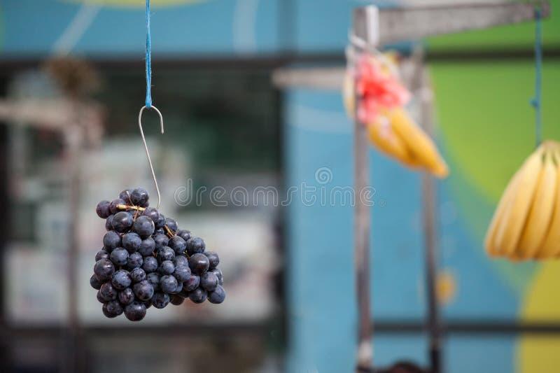 垂悬在一个勾子的天空中的黑葡萄在塞尔维亚的市场上 黑葡萄是在秋天收获的典型的果子 免版税库存照片