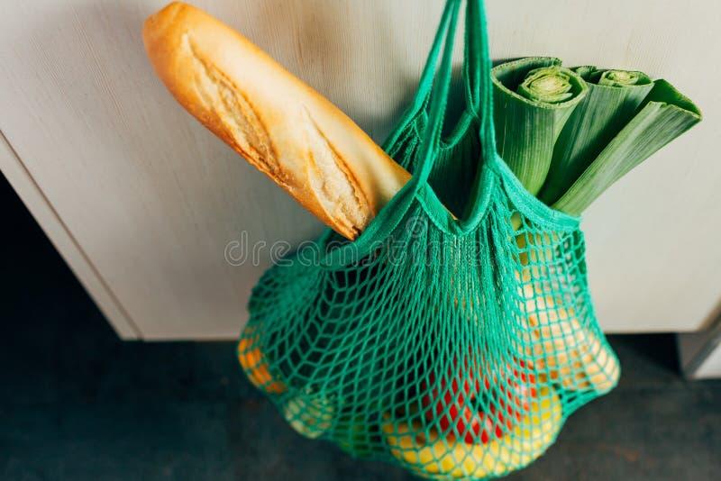 垂悬在一个勾子的绿色串购物袋在厨房里 免版税库存照片