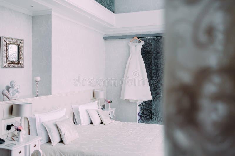 垂悬在一个木挂衣架的白色典雅的新娘礼服在最低纲领派样式的豪华旅馆室 免版税库存照片