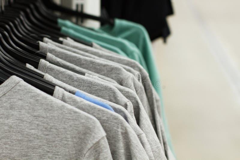 垂悬在一个机架的一些使用的衣裳在跳蚤市场上 礼服背景  选择聚焦 免版税库存图片