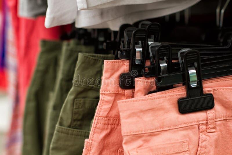 垂悬在一个机架的一些使用的衣裳在跳蚤市场上 礼服背景  选择聚焦 库存图片