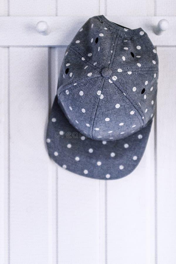 垂悬在一个白色木衣橱的一个被加点的帽子 免版税图库摄影
