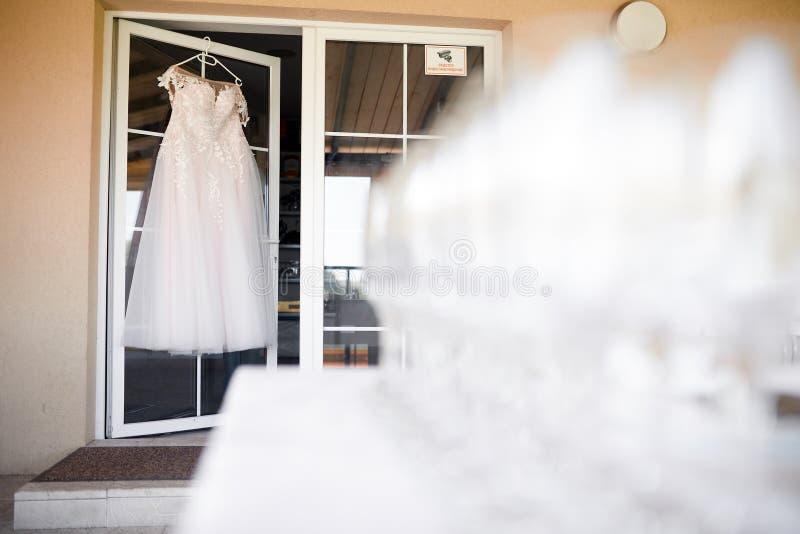 垂悬在一个白色门的一个挂衣架的白色婚纱 免版税库存图片