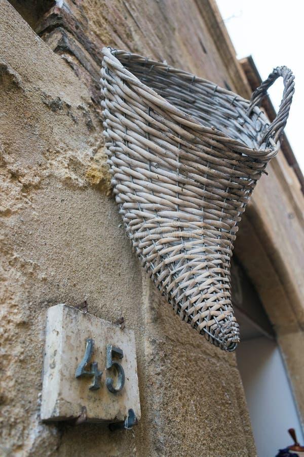 垂悬在一个老托斯坎房子外面的结辨的篮子 免版税库存照片