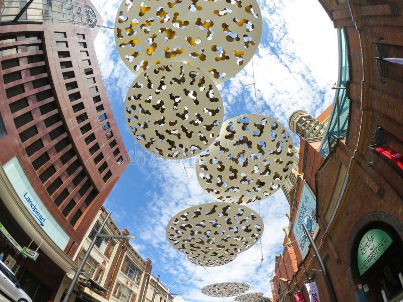 垂悬在一条边路上的偶象抽象圈子雕塑艺术品在Haymarket购物中心前面在中国镇附近 免版税库存图片