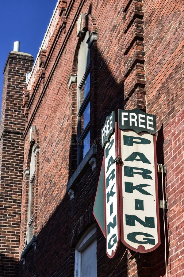 垂悬在一栋老砖瓦房的自由停车处标志 免版税库存照片