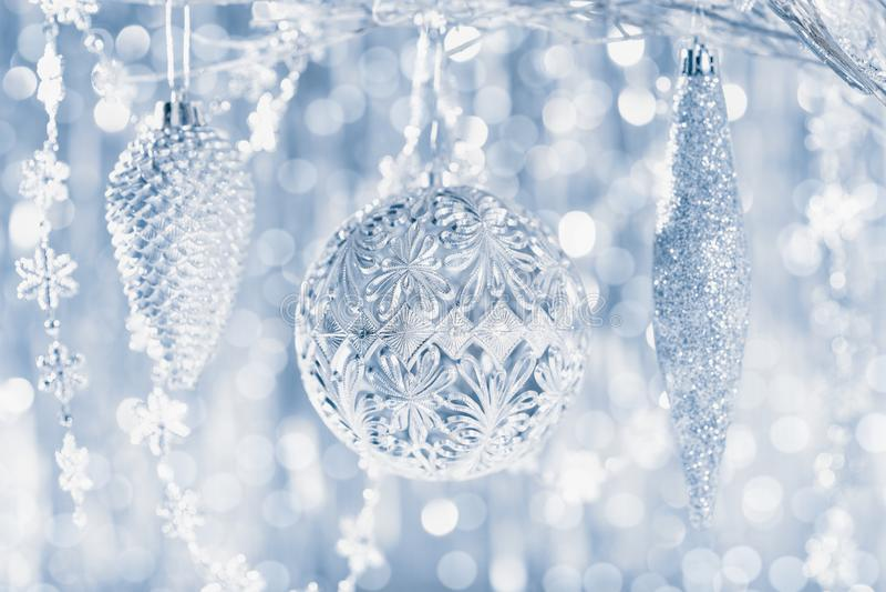 垂悬在一棵树的发光的银色圣诞节装饰品,与defocused圣诞灯在背景中 抽象空白背景圣诞节黑暗的装饰设计模式红色的星形 免版税库存图片