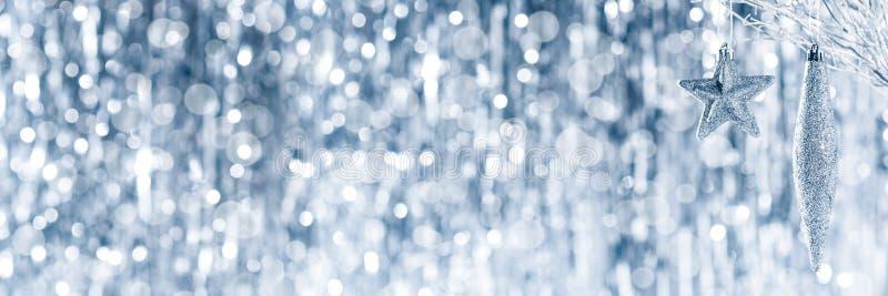 垂悬在一棵树的发光的银色圣诞节装饰品,与defocused圣诞灯 免版税库存图片