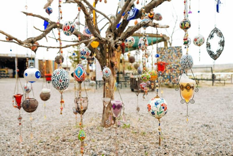 垂悬在一棵死的树的五颜六色的阿拉伯装饰品有白色背景 免版税库存照片