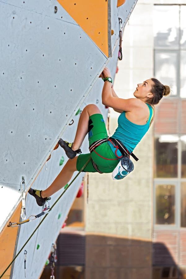 垂悬在上升的墙壁上的逗人喜爱的女运动员 图库摄影