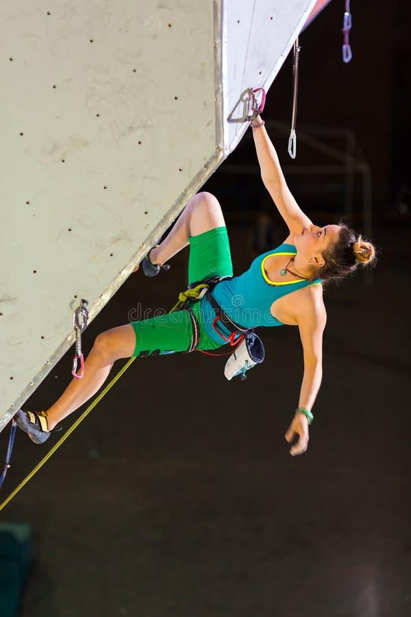 垂悬在上升的墙壁上的逗人喜爱的女运动员 免版税库存图片