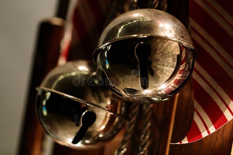垂悬在与一条红色和白色丝带的一个古色古香的木雪橇的2个巨型门铃准备好在假日 库存照片