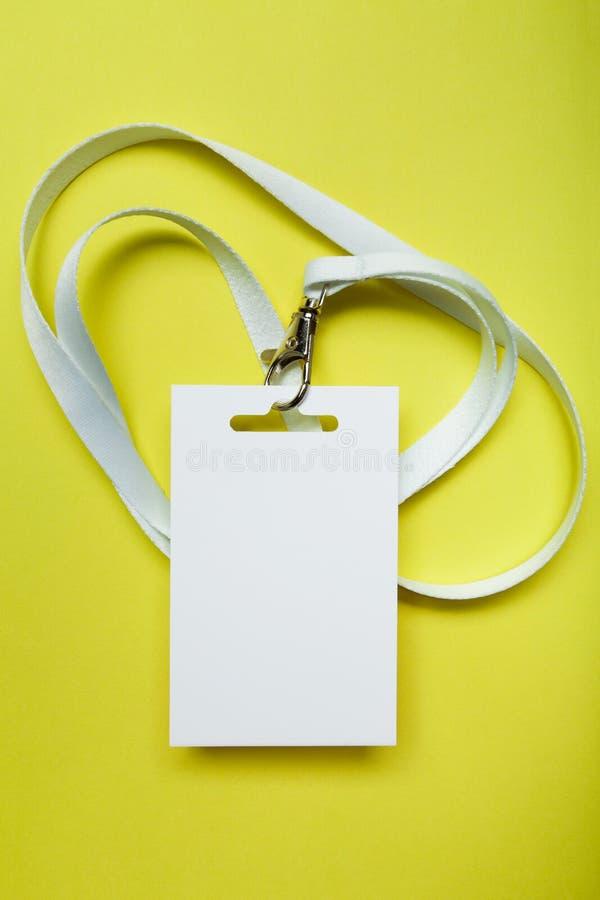 垂悬在与一条红色螺纹的脖子的一个共同的空白的标签名牌 在黄色隔绝的空的布局 库存图片