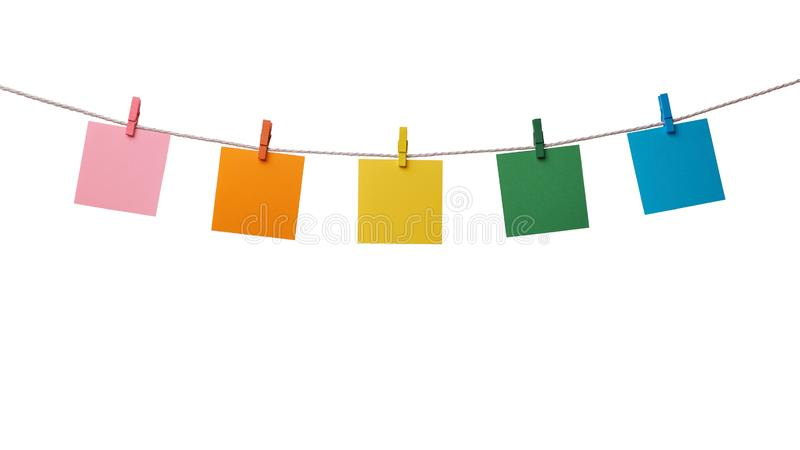 垂悬在与在白色隔绝的木晒衣夹的绳索的五多彩多姿的纸空白的笔记 免版税库存图片