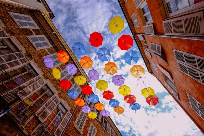 垂悬在与多云天空的大厦中间的五颜六色的伞低角度射击  库存照片