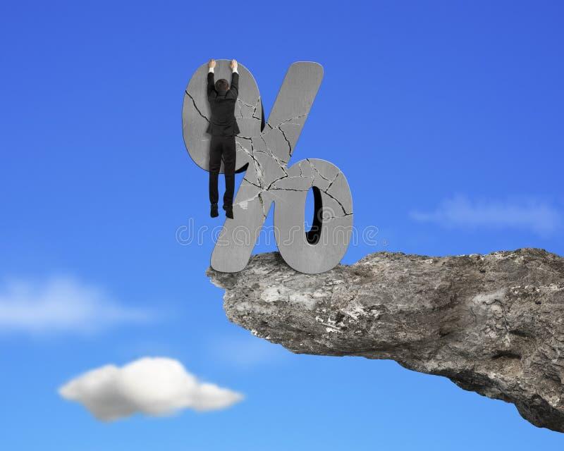 垂悬在与峭壁天空的破裂的百分率符号的商人 免版税库存照片