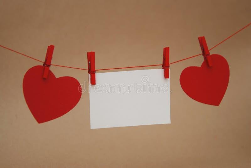 垂悬在与微型晒衣夹的串的红色纸心脏在象牙中立背景 日s华伦泰 装饰重点例证爱 免版税库存图片