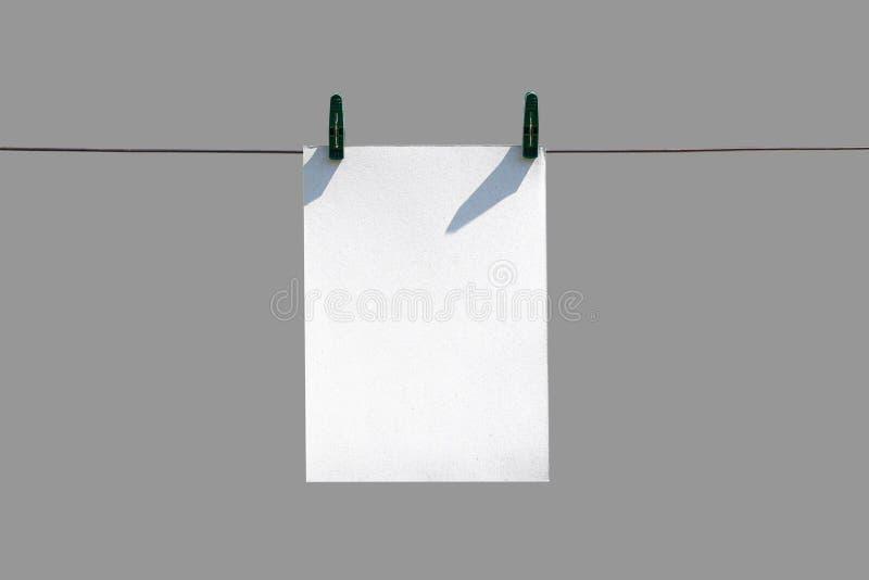 垂悬在与晒衣夹的绳索的白色纸 关闭 免版税图库摄影