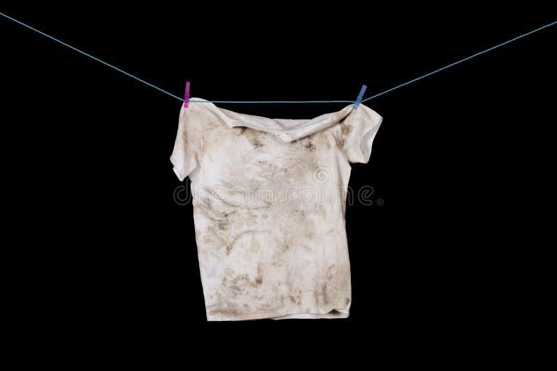 垂悬在与钉的蓝色绳索的肮脏的T恤杉 库存照片