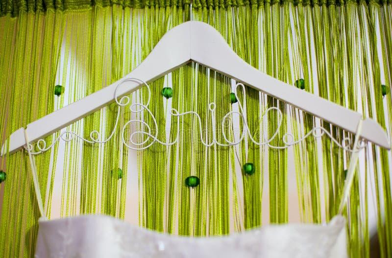 垂悬在与题字`新娘`的装饰挂衣架的白色婚礼礼服 免版税库存图片