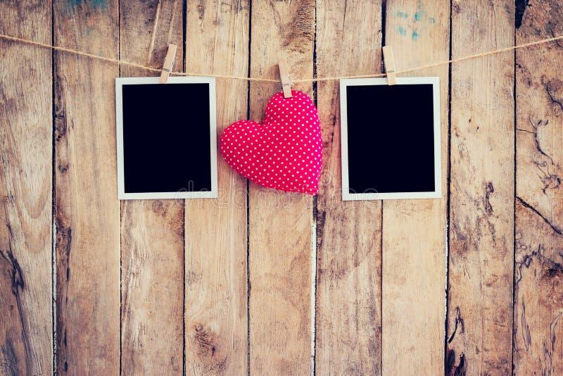 垂悬在与w的晒衣绳绳索的红色心脏和两张照片框架 库存图片