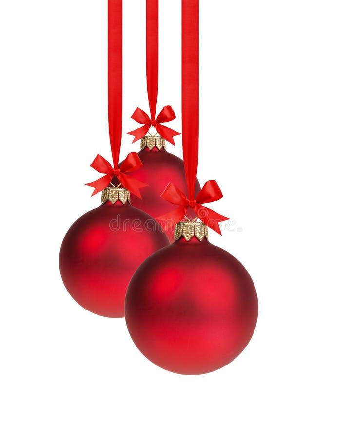 从垂悬在丝带的三个红色圣诞节球的构成 免版税库存图片
