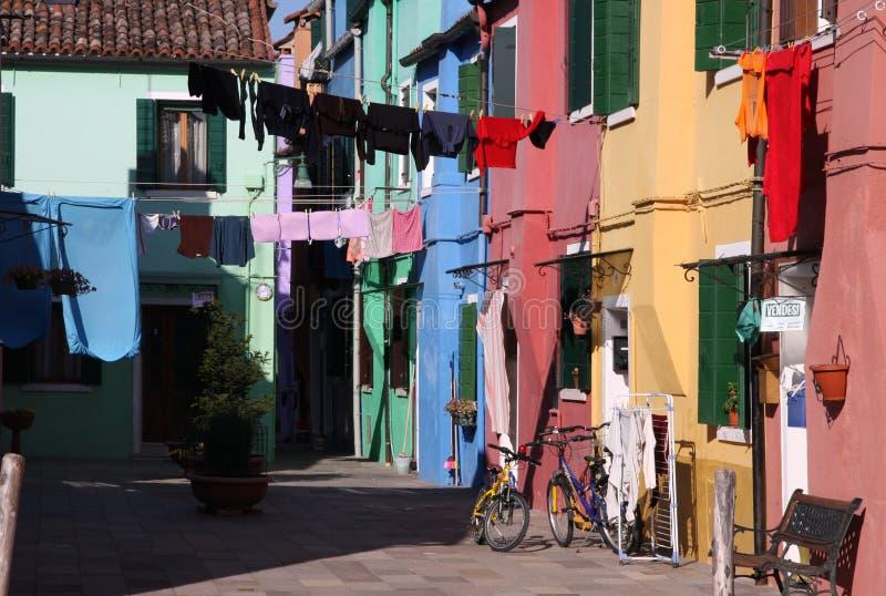 垂悬在五颜六色的房子之间的洗衣店在Burano,威尼斯,意大利 免版税库存照片
