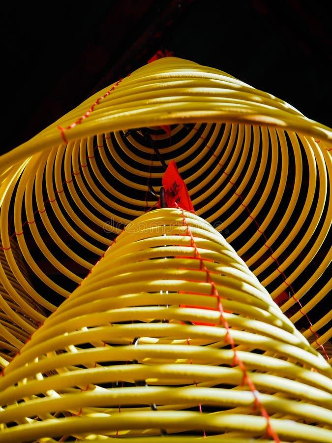 垂悬在从天花板的堆的多大黄色香火卷在中国寺庙 免版税图库摄影