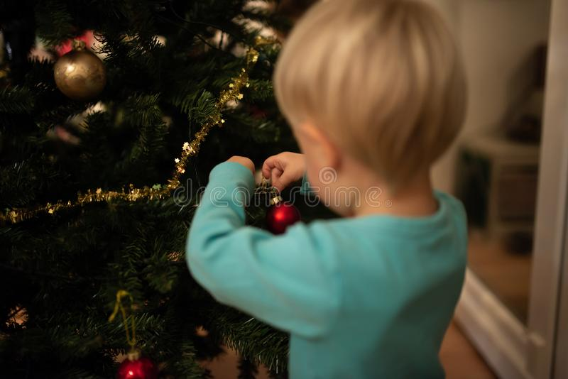 垂悬在假日树的男孩一个红色圣诞节中看不中用的物品 免版税库存照片